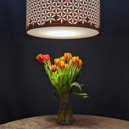 pakabinamas EtnoDesign šviestuvas kabantis virš stalo ant kurio padėtos tulpės